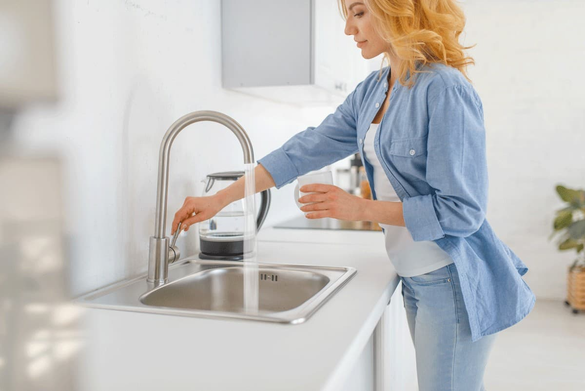 young-woman-with-glass-at-the-sink-on-the-kitchen-MZYTUH8